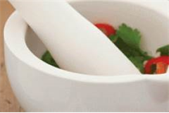 a pestle and mortar with condiments inside