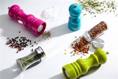 a variety of salt and pepper mills with condiments spread over the table