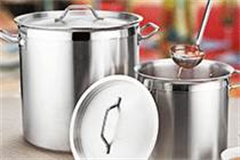 two large stainless steel pots with ladle full of soup