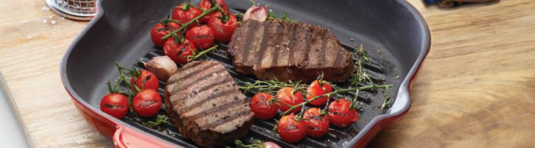 griddle pan with cooked steak and vine ripened baby tomatotoes