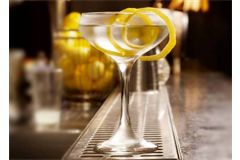 a tall cocktail glass filled with lemon cocktail, decorated with lemon peel