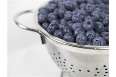 colander with blueberries in