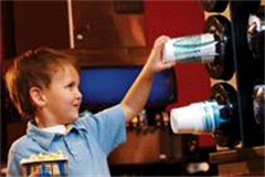 little boy taking cup from a cup dispenser at the cinema