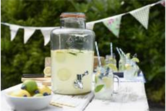 glass drinks dispenser on picnic table containing home made lemonade
