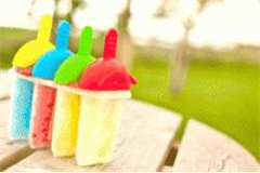 4 different flavoured lollies in lolly moulds, on a park table