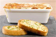oven dish filled with lasagne, placed on a slate alongside two pieces of garlic bread
