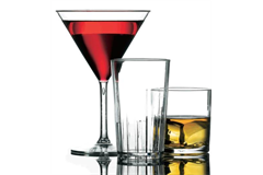 A full martini glass accompanied by an empty high ball tumbler with whiskey glass