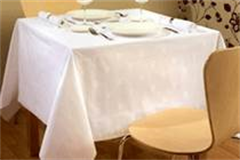 white patterned table linen on a set dinner table