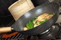 wok on a stove containing chicken and various vegetables