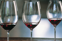 A series of elegant wine glasses in a row each containing red wine