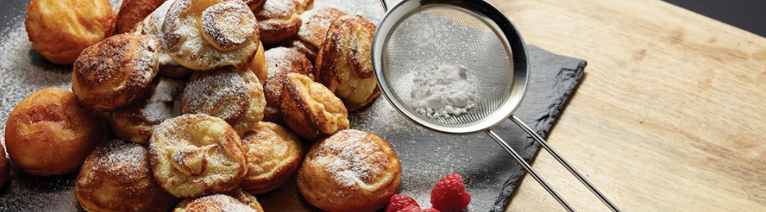 sieve filled with icing sugar accompanied by pastries and raspberries on a slate board